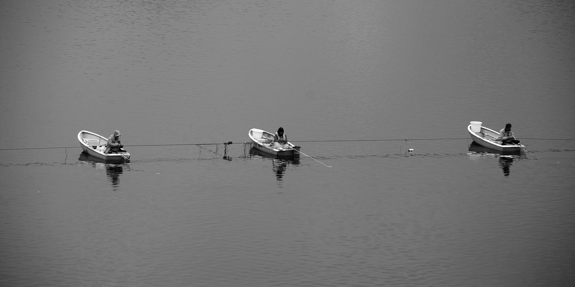 Drei Fischer beim Angeln, jeder in seinem Boot